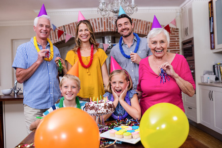 surprise party: Multi-generation family in party hats having fun at birthday party Stock Photo