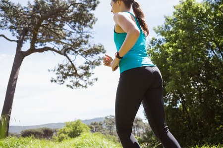 adventuring: Fit smiling woman jogging in the countryside