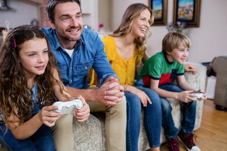 family sofa: Family sitting on sofa and playing video game at home