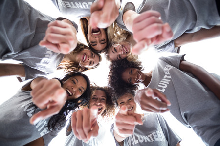 downwards: Happy volunteers pointing downwards against the sky Stock Photo