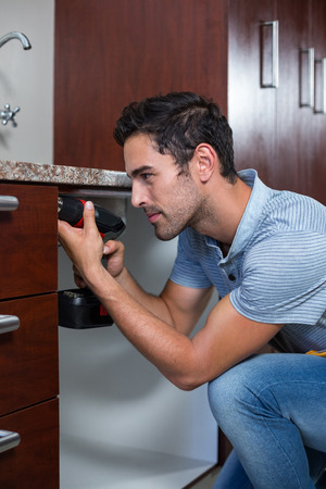 hand drill: Man using cordless hand drill while crouching at home Stock Photo