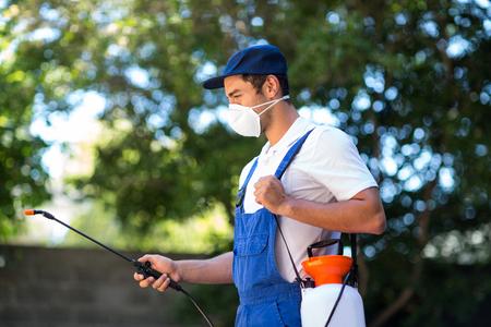 crop sprayer: Side view of worker using crop sprayer in back yard Stock Photo