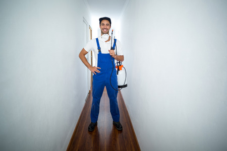pesticide: Portrait of confident pesticide worker standing in hallway at home