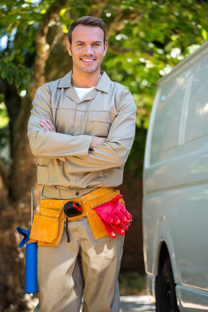 tool belt: Handyman with tool belt around waist standing next to delivery van