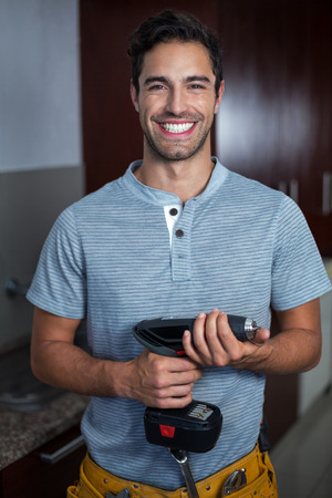 hand drill: Portrait of cheerful man holding cordless hand drill at home