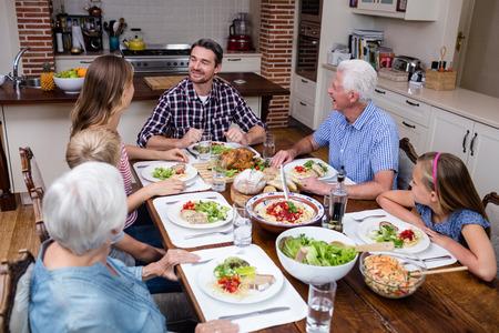Famille multi-génération parler tout en ayant des repas dans la cuisine à la maison