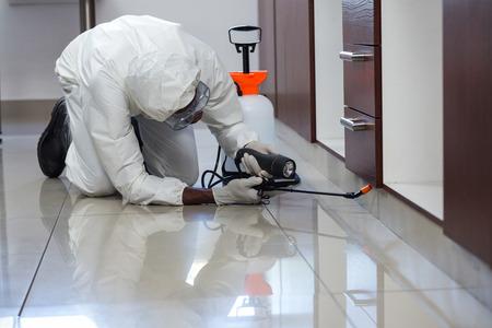 Hubení škůdců muž postřik pesticid pod skříň v kuchyni