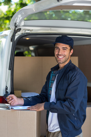 person writing: Portrait of delivery person writing in clipboard while standing by van