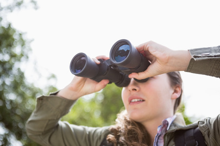 using binoculars: Woman using binoculars in the forest
