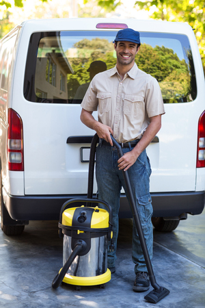 superintendent: Portrait of happy janitor with vacuum cleaner standing against van