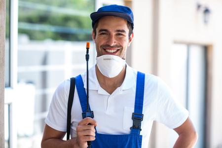crop sprayer: Portrait of happy worker with crop sprayer standing in back yard