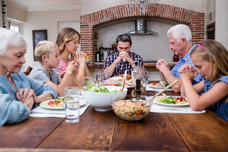 multigeneration: Multi-generation family praying before having meal at home