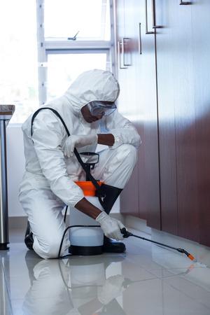 crop sprayer: Pest control man spraying pesticide under the cabinet in kitchen