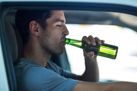 life threatening: Close-up of man drinking alcohol while sitting in car Stock Photo