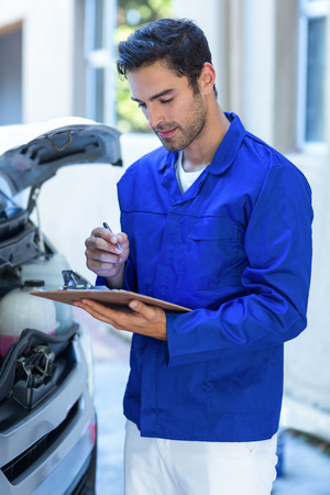 engineering clipboard: Male engineering checking clipboard while standing by van Stock Photo