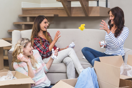 each other: Playful friends throwing packing peanuts with each other in their new house
