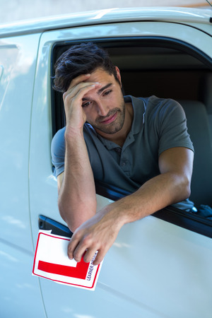 l hand: Depressed man with head in hand holding L pate in car Stock Photo