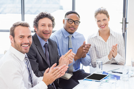 applauding: Portrait of businesspeople applauding while in a meeting at office