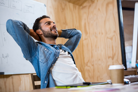 ejecutiva en oficina: Sirva la relajación en silla con las manos detrás de la cabeza en la oficina