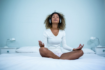 head phones: Woman listening to music on head phones while meditating on bed in bedroom