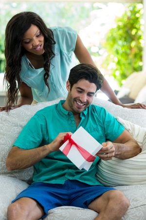 unwrapping: Woman watching a man while unwrapping a gift at home