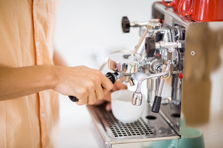 Mid section of man preparing coffee from coffeemaker at home Stock Photo
