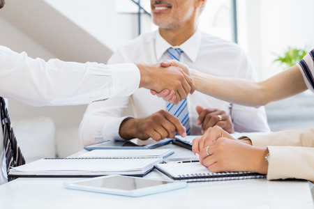 businessmen shaking hands: Businessmen shaking hands with businesswomen in the office Stock Photo