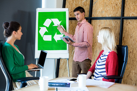 environmental conversation: Colleagues discussing with recycling sign on white board in the office