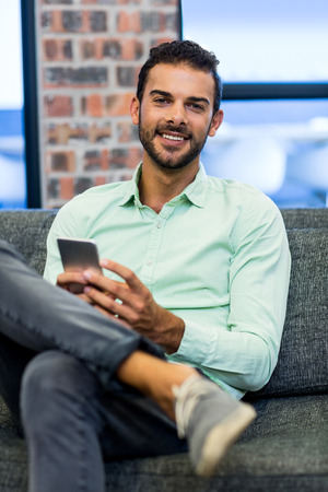 text messaging: Young man text messaging on mobile phone in the office