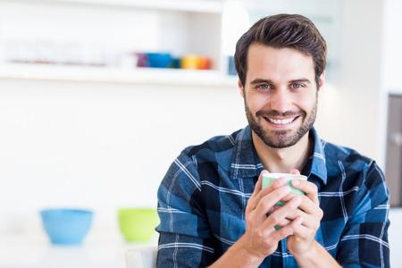 Ritratto di uomo felice con una tazza di caffè in cucina