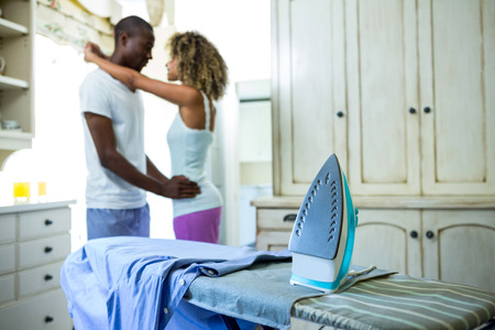 ironing board: Iron and a shirt on ironing board and couple embracing in background