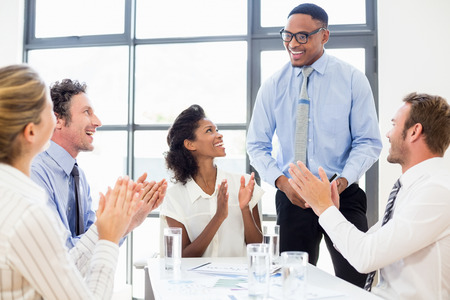 applauding: Business team applauding a colleague in meeting