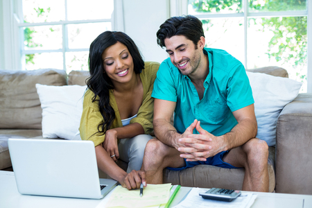 Happy couple with laptop discussing on bills at home