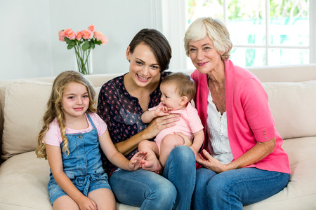 carying: Happy multi generation family with baby while sitting at home