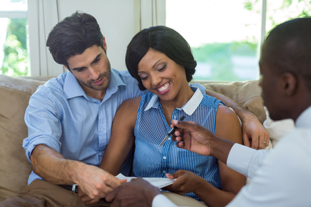 contract signing: Happy couple signing contract with real estate agent at home