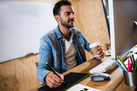 graphics tablet: Man working on his graphics tablet and holding coffee in office