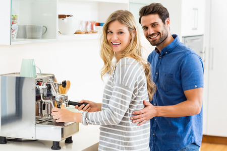 Portrait of young couple preparing coffee from coffeemaker at home Stock Photo