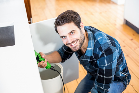 drill floor: Portrait of man fixing kitchen sink in the kitchen Stock Photo