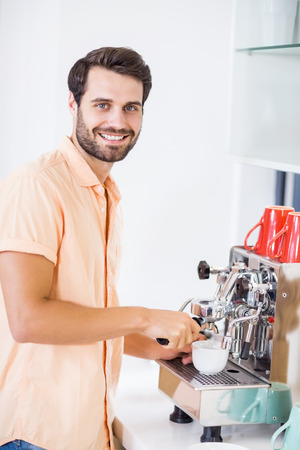 coffeemaker: Portrait of man preparing coffee from coffeemaker at home