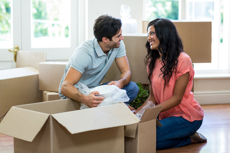 unpacking: Young couple assisting each other while unpacking carton boxes in new house Stock Photo