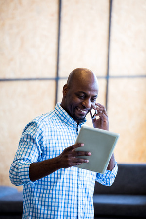 Man looking at digital tablet while talking on phone in office Stock Photo