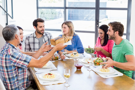 interacting: Friends interacting while having a meal at dining table Stock Photo