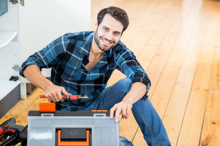 Portrait of man unpacking his tool box at home Imagens