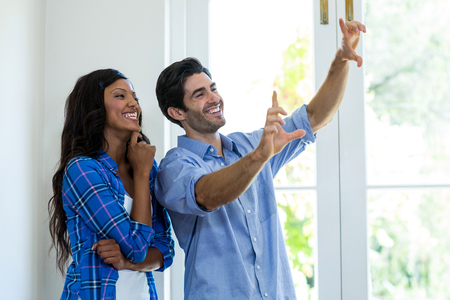 framing: Couple framing a picture with hands at home Stock Photo