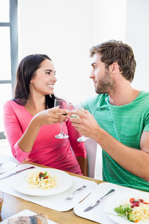 toasting wine: Young couple toasting wine glass at home Stock Photo