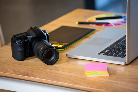 graphics tablet: Camera, sticky notes, graphics tablet and laptop at desk in office