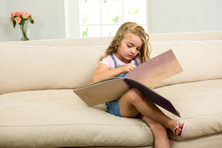picture book: Girl with picture book while sitting on sofa