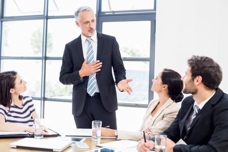 Un homme d'affaires est debout devant ses collègues et parle au travail Banque d'images
