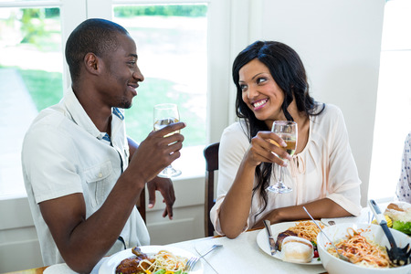 Young couple talking while having meal in kitchen at home