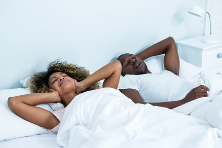 snoring: Woman ignoring while man snoring on bed in bedroom
